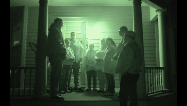 The Central Iowa Ghost Society gathers on the porch of the historic Gallup House before an investigation there last month.