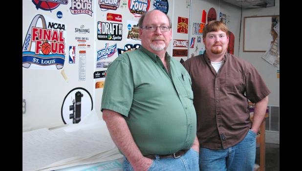 Paul Ogren (left) and son Adam Ogren in their Jefferson sign shop, Ogren's Custom Graphics. The shop's walls are adorned with examples of their work, including graphics to adorn basketball backstops, ball carts and other products manufactured locally by Spalding.