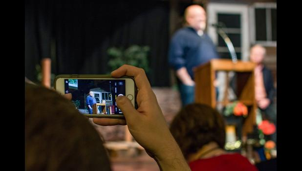 An audience member holds up their phone Saturday night at History Boy Theatre to snap a photo of Kevin Scott, chief technology officer at Microsoft, speaking in Jefferson alongside other leaders from Silicon Valley. PHOTO BY MATT WETRICH