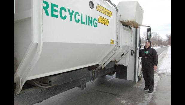 Recycling truck operator Craig Kinsey watches as the truck lifts a bin of recyclables overhead Tuesday on South Street in Jefferson.