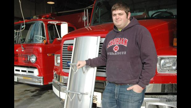 Garrett Riedesel, assistant chief of the Churdan Fire and Rescue Department, displays one of the metal panels that can interlock to form an escape tube around a farmer buried in grain. A group of local farmers recently gave the department enough money for a grain bin rescue kit, the first of its kind in the county.