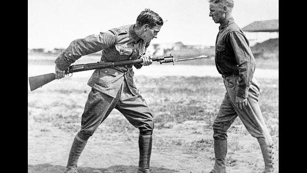 An American soldier (left) undergoes bayonet fighting instruction by an English sergeant major at Camp Dick, Texas, between 1917 and 1918.