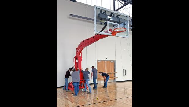 A crew from AAI/Spalding installs an Arena Renegade backstop this fall at Greene County High School.