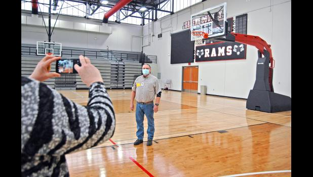 Juhl Carstens, who works in shipping at AAI/Spalding, gets his picture taken with one of two Arena Renegade backstops recently donated by the company to Greene County High School. Usually, he said, production staff only ever gets to see the fully assembled units on TV during NBA games like everyone else. ANDREW McGINN | JEFFERSON HERALD