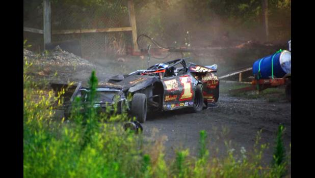 """Jon Strabley sits unconscious in the driver's seat of his flattened race car July 13 at the Boone Speedway following a harrowing crash on turn number three at more than 80 mph. First responders had yet to arrive. The crash has tested the Strabley family of Grand Junction and their decades-old love of auto racing. """"How can you tell someone you can't live your dream?"""" dad Rob Strabley asks. CARLA SHEPPARD PHOTO"""
