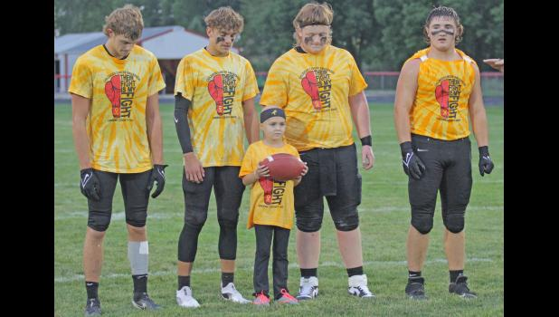 Avril Shahan (middle) is battling another bout with Leukemia and was honored as the child captain for Greene County's annual Childhood Cancer Awareness night Sept. 3 in Jefferson. She's pictured with Ram captains, from left; Jackson Morton, Bryce Stalder, Mason Stream and Bradyn Smith.  BRANDON HURLEY   JEFFERSON HERALD