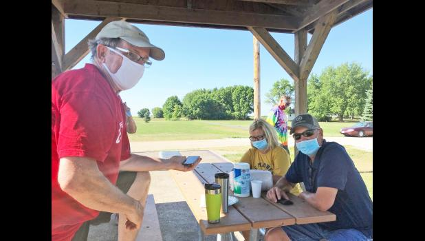 Chuck Offenburger (left) talks to Terry Rich by speakerphone as Doug and Karen Lawton listen in Friday, July 24 during a Cooper RAGBRAI anniversary celebration.  BRANDON HURLEY | JEFFERSON HERALD