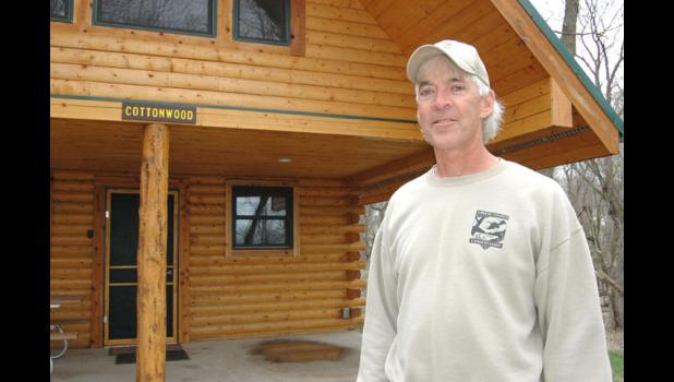 County conservation director Dan Towers stands in front of the first finished cabin at Spring Lake Park. Towers is at work building a second cabin next door, which should be complete by Memorial Day.