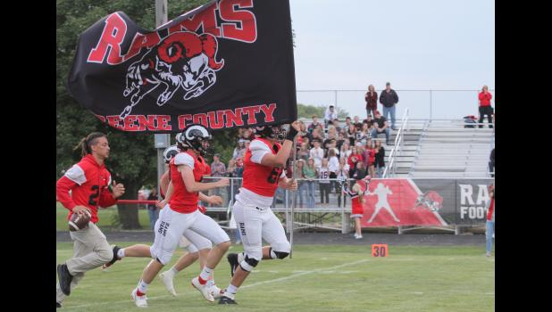 Greene County senior Tyler Miller carries the Ram flag out onto the field prior to their 54-0 victory over Perry Aug. 30 in Jefferson.  BRANDON HURLEY | JEFFERSON HERALD