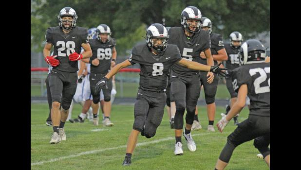 Greene County's Max Riley (8) celebrates with Bryce Stalder (5) and Nate Black (28) following a first quarter touchdown, one of the Rams' five in the opening frame, which led to a decisive 63-0 win over Perry Sept. 3 in Jefferson.  BRANDON HURLEY   JEFFERSON HERALD