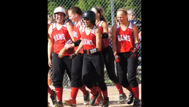 Junior Hannah Onken (far left)  is greeted by her team mates after hitting her second home run in a regional final game versus  Sioux Center on July 14. The Rams won the game 12-3 and earned a spot in the 3A state softball tournament.