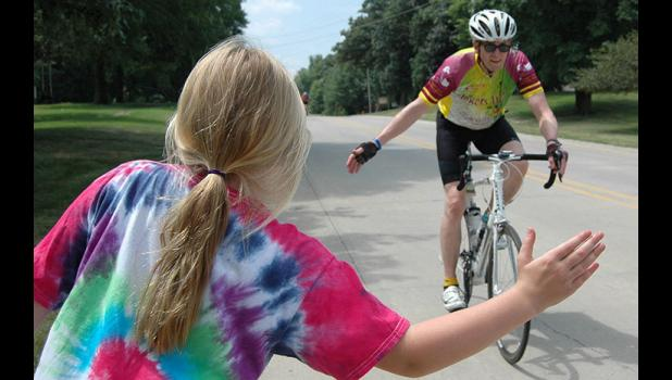 Lucy VanderLinden, 10, readies a high five outside her house at Westwood Drive and Hillcrest Place as a cyclist makes his way Monday afternoon into Jefferson from the west. ANDREW McGINN | JEFFERSON HERALD