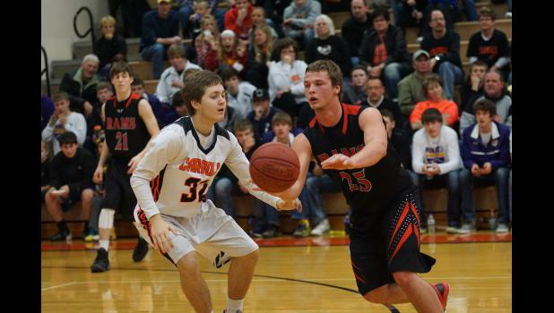 Senior Riah Nelsen tries to avoid pressure from Carroll's  Zach Riddle so he can get the ball to a teammate in Rams district tournament game on Feb. 23.