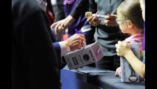 Kuemper Catholic graduate and Toronto Raptors head coach Nick Nurse signs his own bobble head while his hand is graced with the 2019 NBA championship ring at an Iowa Wolves game Nov. 15 in Des Moines.  BRANDON HURLEY | TIMES HERALD