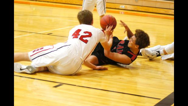 Ram sophomore Sico Boateng and Ballard's Nick Hartman fight for a loose ball in the Rams' tournament game versus Ballard on Feb. 25. The Bombers won the game 82-63 and ended the Rams' 2013-2014 season.