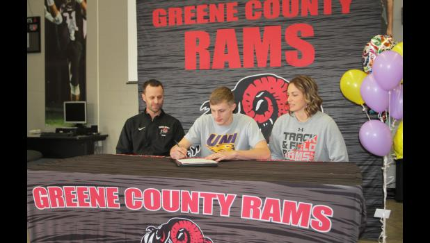 Greene County's Carter Morton (middle) signed a letter of intent with the University of Northern Iowa on Jan. 8. He's seen here with his parents, Chad (left) and Deb (right) at the high school in Jefferson.  BRANDON HURLEY | JEFFERSON HERALD