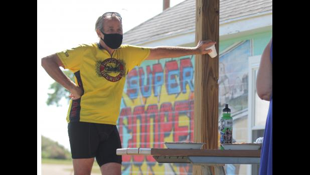 Panora resident Jim Siavers listens in on a RAGBRAI anniversary meeting Friday, July 17 in Cooper, 40 years after the annual bike ride's mid-day stop. Seavers stands in front of a Cooper town mural painted on an old weigh station along the Raccoon River Valley Trail.  BRANDON HURLEY | JEFFERSON HERALD