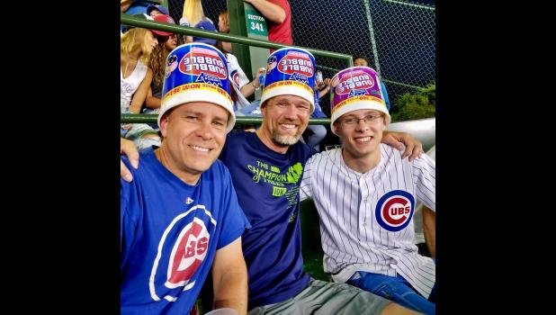 Kyle McAleer (right) was struck in the head by a pipe that fell from Wrigley Field's scoreboard last week. He put on a bucket with his father Scott (left) and a friend shortly before the pipe fell.