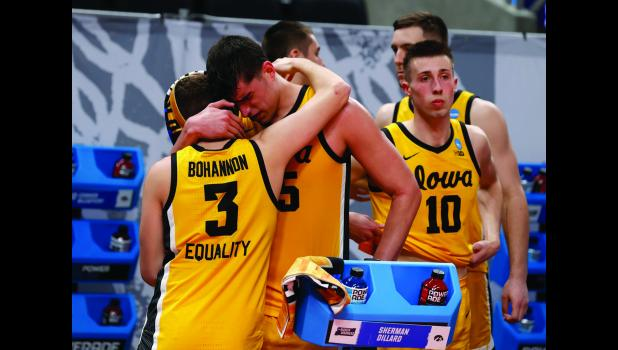 Iowa Hawkeyes center Luka Garza (55) hugs guard Jordan Bohannon (3) following their loss to the Oregon Ducks in the second round of the 2021 NCAA Men's Basketball Tournament Monday, March 22, 2021 at Bankers Life Fieldhouse in Indianapolis. (Brian Ray/hawkeyesports.com)