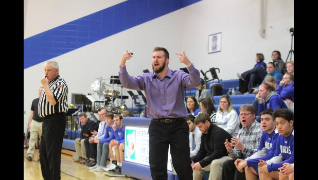 Perry boys' basketball head coach and 2011 East Greene grad, Aaron Lyons (front), shouts out encouragement as his dad and PHS assistant, Dean (sitting) reacts to a call during the Bluejays game against Ogden this past December.  BRANDON HURLEY | JEFFERSON HERALD