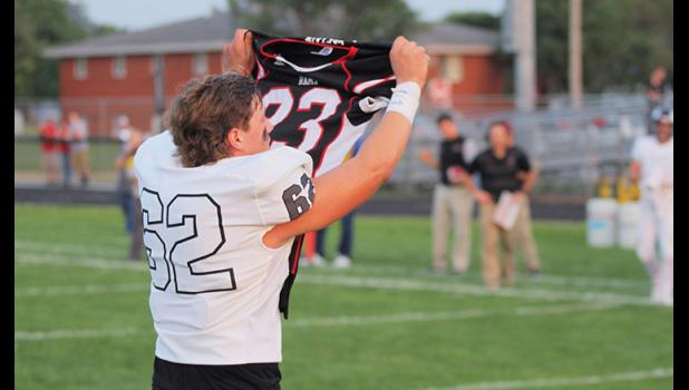 Hoyle hoists Martin's jersey toward the crowd Friday in Perry. The Rams won the 2018 season opener.