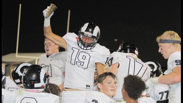 Greene County senior David Richter (19) celebrates the Rams' rivalry win over Perry by giving the historic Cowbell a rings. Greene County was a 14-6 victor in week one, Friday, Aug. 24 in Perry.  BRANDON HURLEY | JEFFERSON HERALD