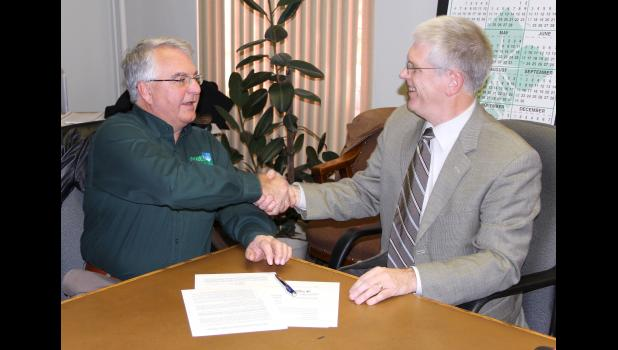 Wild Rose president Tom Timmons (right) and Norm Fandel, president of the Greene County not-for-profit associated with the planned Jefferson casino, shake hands after signing an application that will be delivered to the Iowa Racing & Gaming Commission.