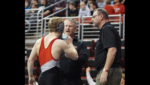 Jordan Challen gets instructions from his assistant coach (and father) Eric Challen and head coach Mark Sawhill during a consolation match on Friday night.