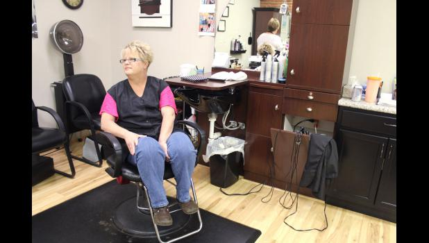 Karen Renslow sits at her station at Head Masters in Jefferson, where she cuts hair.