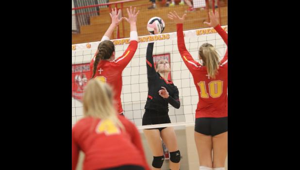 MARK SCHAFER | TIMES HERALD Greene County's Harleigh Weir (middle) sends a spike past the Kuemper defense of Kara Peter (left) and Sophie Badding (10) during a first round regional match held Oct. 23 at Kuemper. The No. 2 ranked Kuemper team beat Greene County 3-0.