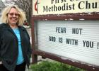 """ABOVE: The Rev. Julie Poulsen, of the First United Methodist Church in Jefferson, changed the message on the church's sign when the COVID-19 pandemic reached Iowa. With Iowans prohibited from gathering in groups of more than 10, she's been livestreaming services from an empty church. """"I've never had a church empty on Easter,"""" she says. TOP: Stained glass at the First United Methodist Church in Jefferson depicts Christ in prayer in the Garden of Gethsemane, the site of his betrayal and arrest."""