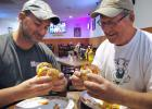 Brett Cranston (left), owner of Doc's Stadium, and Mike Holden of Moo Meat prepare Monday to down The Carnivore, their new, jointly designed burger.