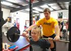 Strength and conditioning coach Richard Beeler assists volleyball player Annie Palmer with her lift.  Beeler has been running the program since last February.